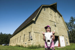 A young visitor holds a bison skull, standing in front of the historic barn
